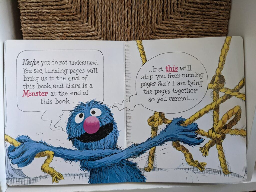Grover tying the pages together so you cannot turn pages.
